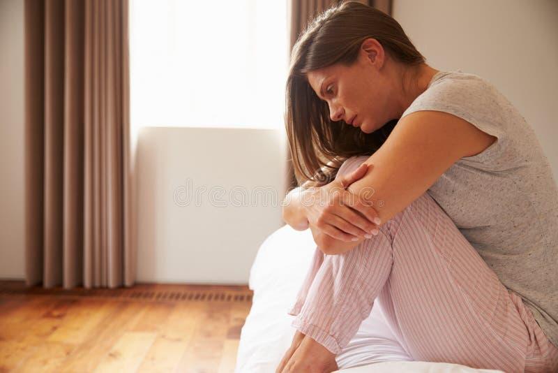 Kobiety cierpienie Od depresji obsiadania Na łóżku W piżamach zdjęcia royalty free