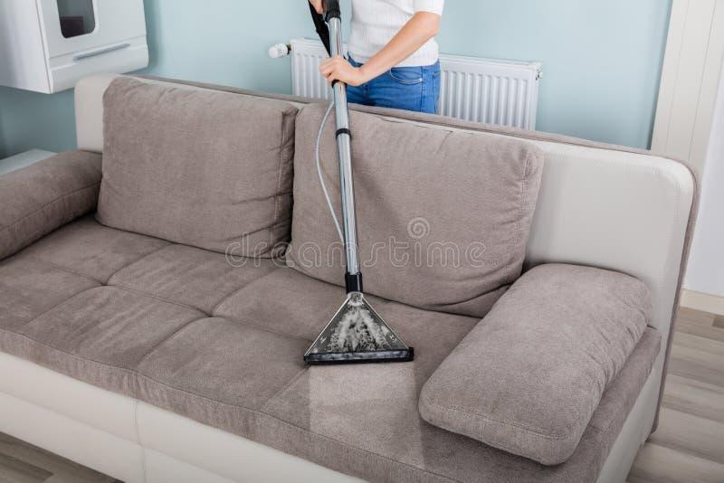 Kobiety cleaning kanapa z próżniowym cleaner zdjęcie royalty free