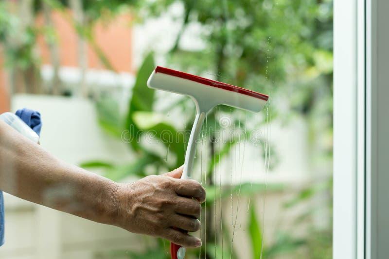 Kobiety cleaning okno z kiść detergentem obraz stock