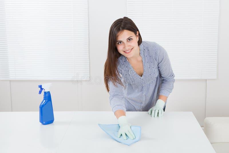 Kobiety cleaning stół z cleanser i łachmanem w domu obraz stock