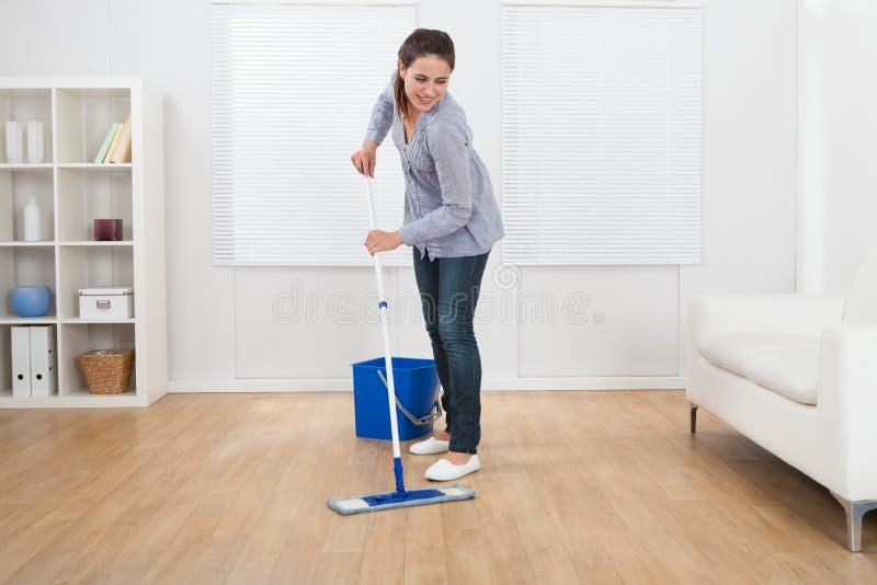 Kobiety cleaning twardego drzewa podłoga żywy pokój zdjęcie stock