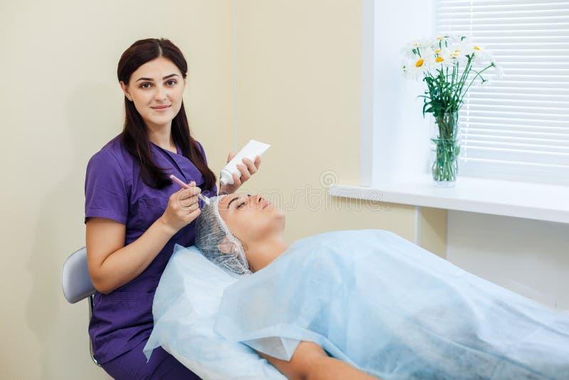 Kobiety cosmetologist stosować maskę na twarzy kosmetyczne procedury zdjęcie royalty free