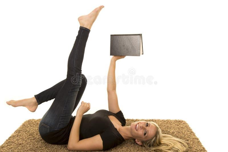 Kobiety czytanie jest ubranym czerń kłaść na tylnej chwyt książce, nogach up i zdjęcia royalty free