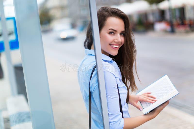 Kobiety czytelnicza książka podczas gdy czekający autobus fotografia stock
