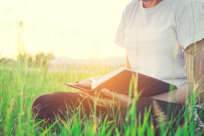 Kobiety czytelnicza książka przy parkowym zmierzchu światłem fotografia royalty free