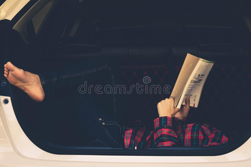 Kobiety czytelnicza książka w końcówce samochód podczas wakacje fotografia stock