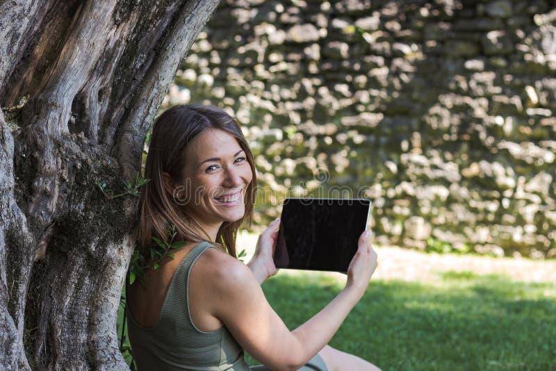 Kobiety czytelnicza pastylka i cieszy si? odpoczynek w parku pod drzewem obraz royalty free