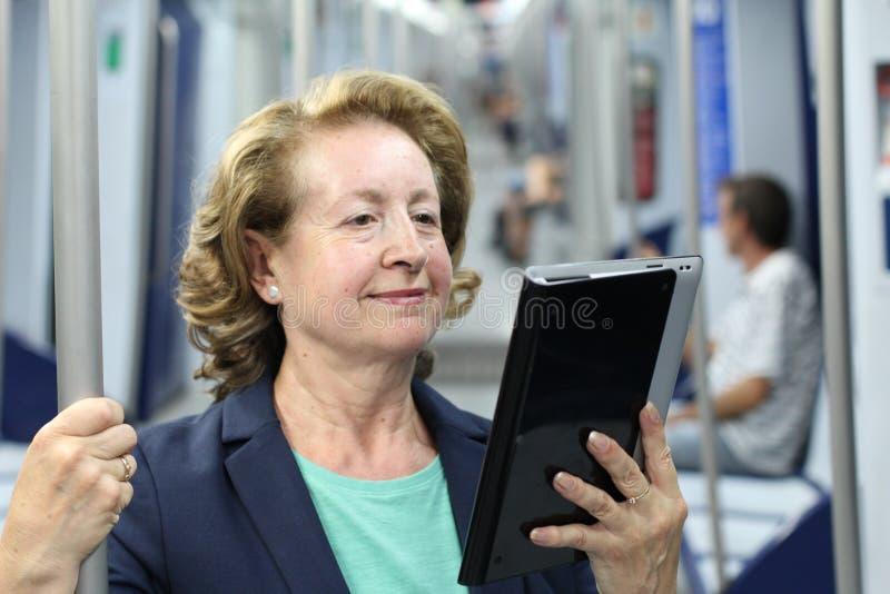Kobiety czytelniczy ebook na taborowym metra metrze obraz stock