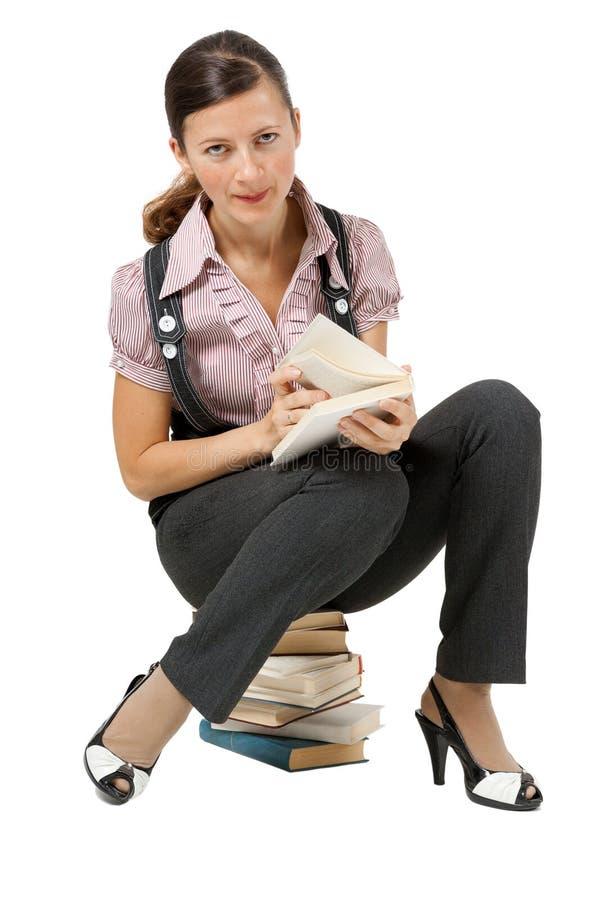 Kobiety czytelniczy obsiadanie na stosie książki obraz royalty free