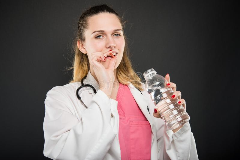 Kobiety doktorska bierze pigułka z butelką woda obrazy royalty free