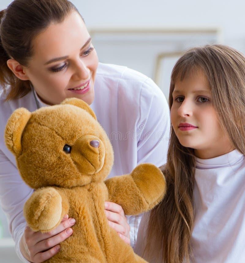 Kobiety kobiety doktorska egzamininuje ma?a ?liczna dziewczyna z zabawka nied?wiedziem fotografia stock