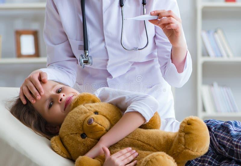 Kobiety kobiety doktorska egzamininuje ma?a ?liczna dziewczyna z zabawka nied?wiedziem fotografia royalty free