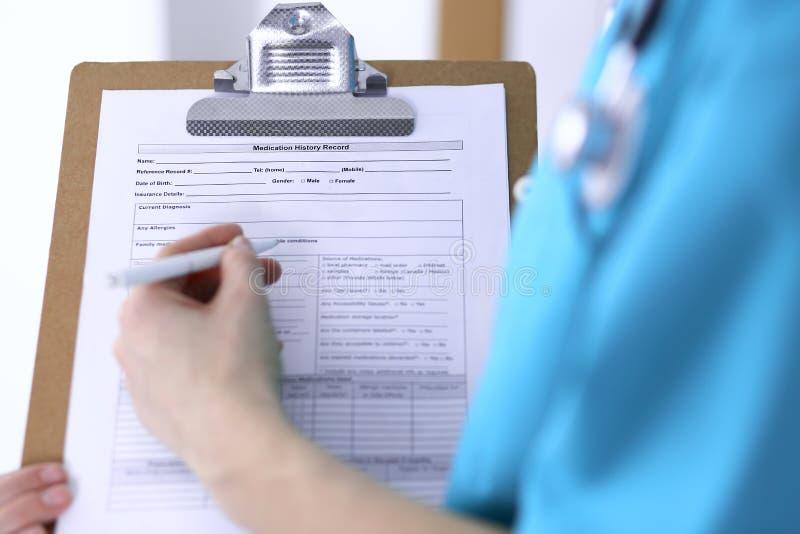 Kobiety doktorski plombowanie w górę medycznej formy na schowka zbliżeniu Lekarz kończy up egzamininować jego pacjenta w szpitalu obrazy stock