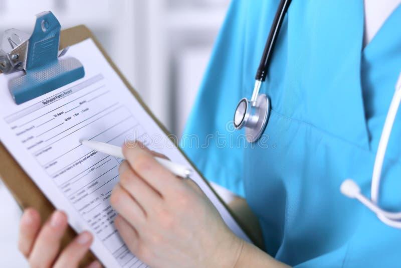 Kobiety doktorski plombowanie w górę medycznej formy na schowka zbliżeniu Lekarz kończy up egzamininować jego pacjenta w szpitalu fotografia royalty free