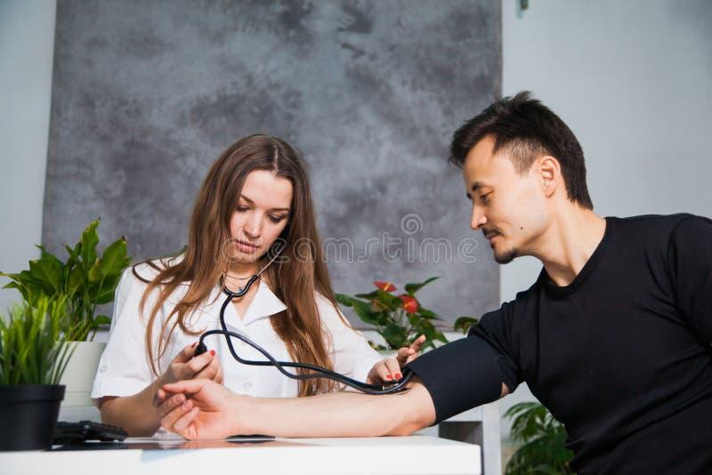 Kobiety doktorski pomiarowy arterialny ciśnienie krwi dla pacjenta przy kliniką zdjęcie stock