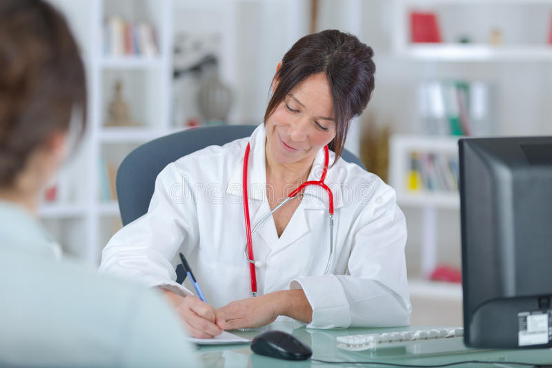 Kobiety doktorski słuchanie patientin biuro zdjęcia royalty free