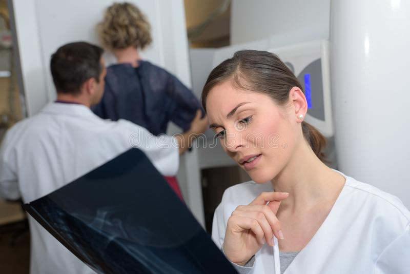 Kobiety doktorski sprawdza xray zdjęcia stock