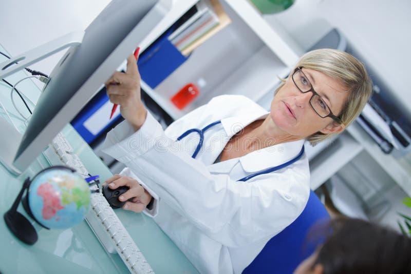 Kobiety doktorski wskazywać ekran komputerowy z zdziwionym zdjęcie stock