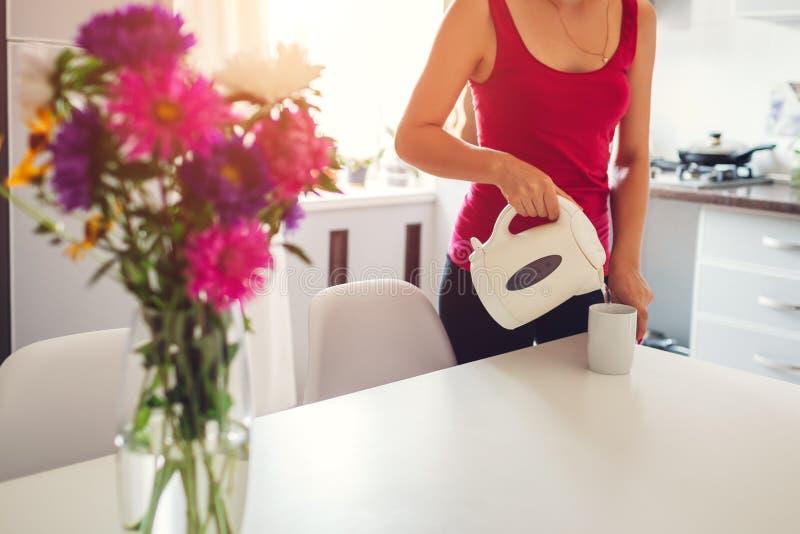 Kobiety dolewania gorąca woda od elektrycznego czajnika w kuchni Dziewczyna robi herbaty nowoczesna kuchnia projektu zdjęcie stock