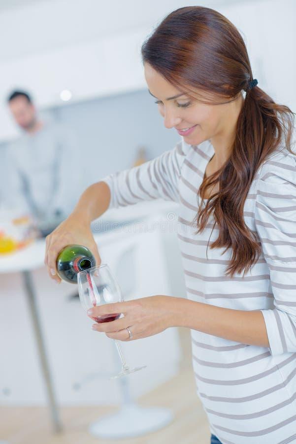 Kobiety dolewania herself szklany czerwone wino zdjęcie stock