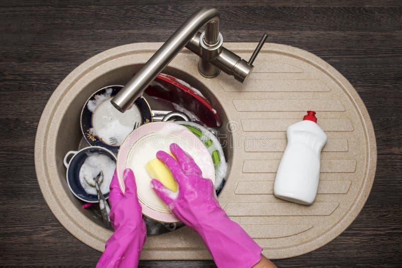 Kobiety domycia naczynia w kuchni Zamyka up kobiety r?ka Gospody? domowych czy?ci naczynia Sprz?tanie w kuchni obraz royalty free