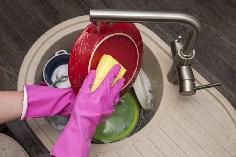 Kobiety domycia naczynia w kuchni Zamyka up kobiety r?ka Gospody? domowych czy?ci naczynia Sprz?tanie w kuchni obrazy royalty free