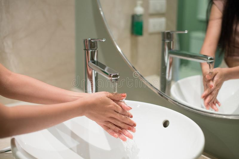 Kobiety domycia ręki pod faucet z wodą obraz stock