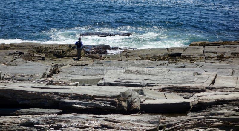 Kobiety dopatrywania ocean przy skalistym dennym wybrzeżem 2 zdjęcia stock