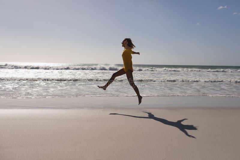 Kobiety doskakiwanie na plażowym pobliskim seashore obrazy stock