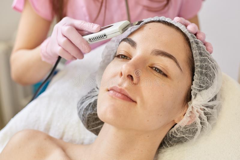 Kobiety dostawanie czyści terapię z fachowym ultrasonic wyposażeniem w kosmetologii klinice, chce mieć odświeżenie zdjęcia royalty free