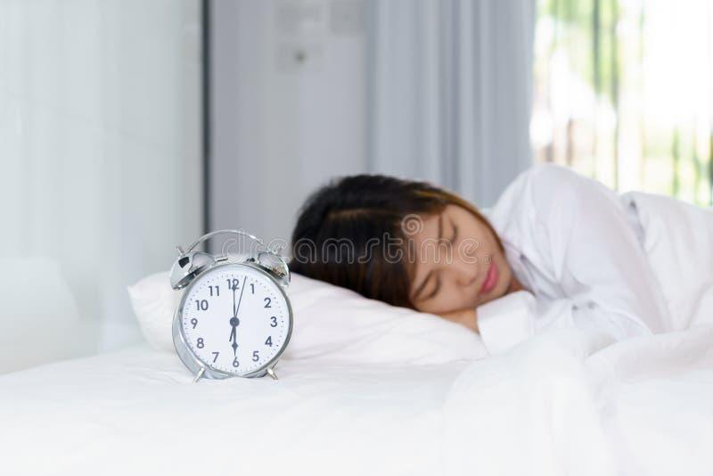 Kobiety dosypianie na łóżku w ranku z budzikiem zdjęcia royalty free