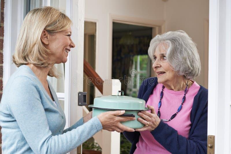 Kobiety dowiezienia posiłek Dla Starszego sąsiad zdjęcia stock