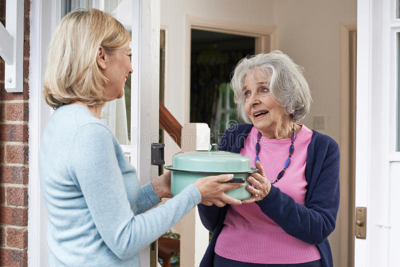 Kobiety dowiezienia posiłek Dla Starszego sąsiad obrazy royalty free
