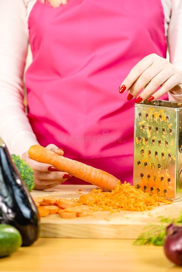 Kobiety drażniąca marchewka na metalu grater obrazy stock