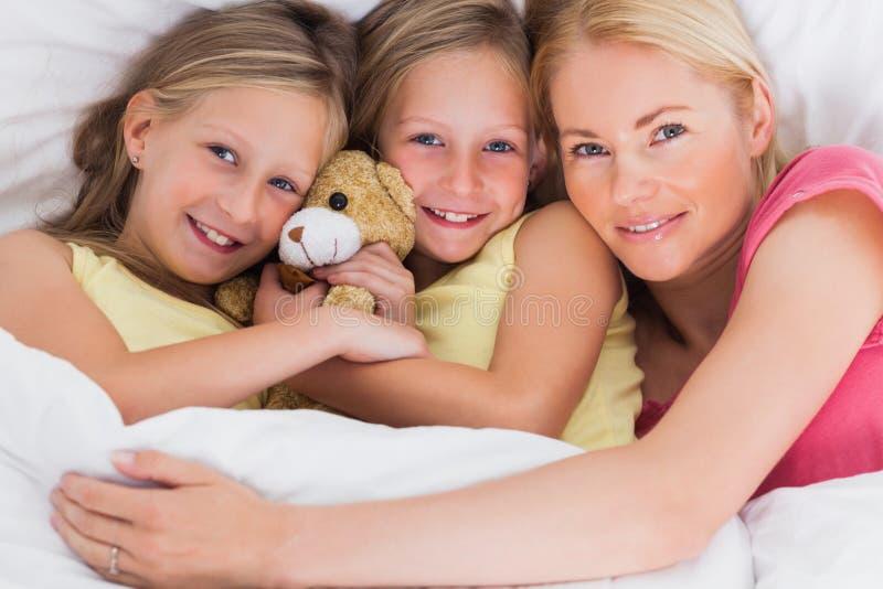 Kobiety drzemanie w łóżku z jej ślicznymi dziećmi obrazy royalty free