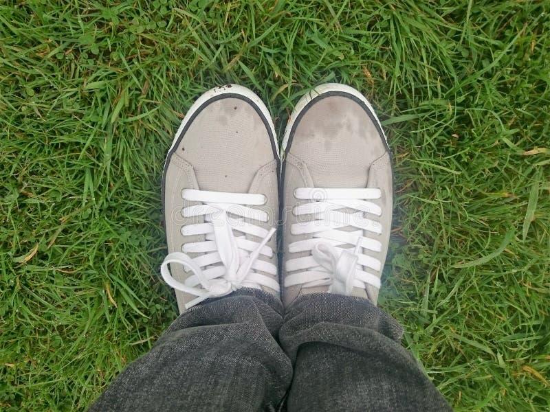 Kobiety dysponowane w sneakers na mokrej trawie fotografia royalty free