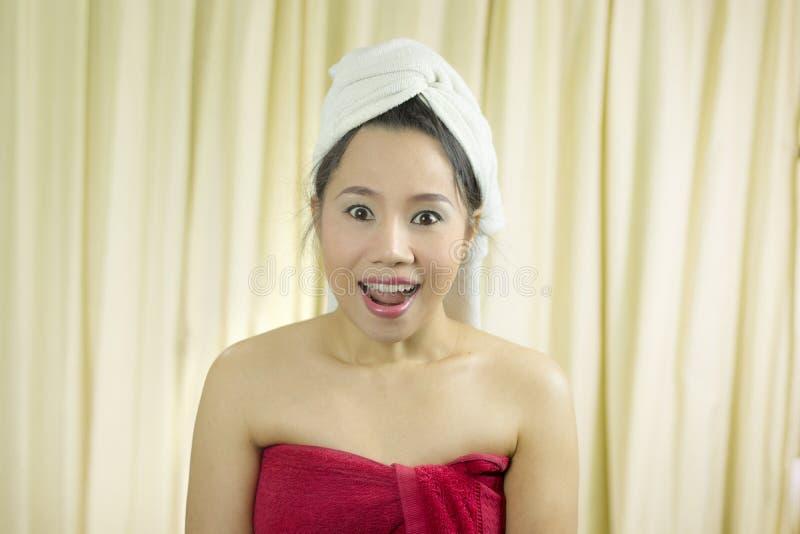 Kobiety działania uśmiech śmieszny, smutny, jest ubranym spódnicę zakrywać jej pierś po obmycie włosy, Zawijającego w r zdjęcia stock