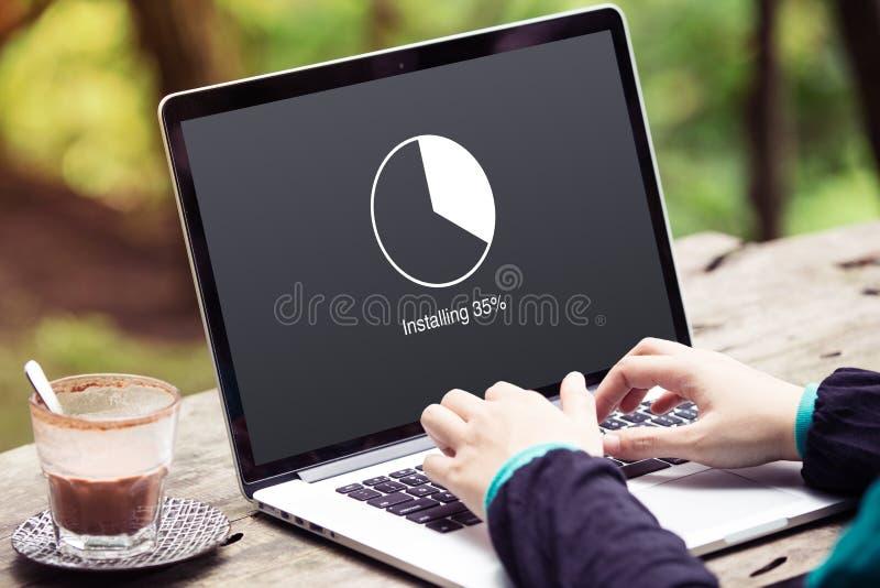 Kobiety działanie i Instalować aktualizacja z okręgu ładunku odsetka czekania wskaźnika pojęciem na laptopie, komputerze/ obrazy stock