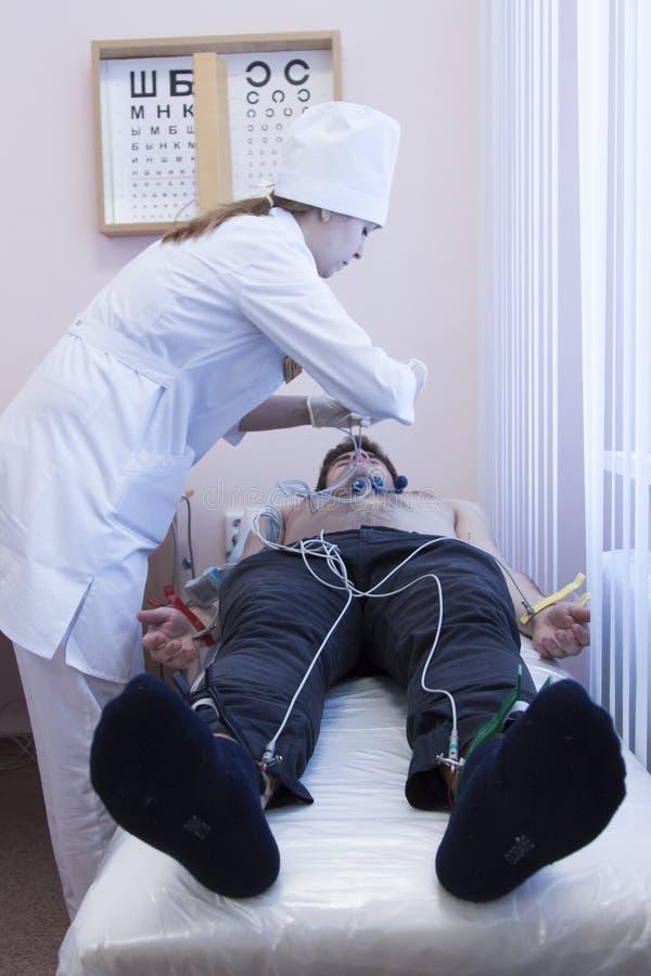 Kobiety ECG doktorski analizuje elektrokardiogram pacjent w przy szpitalem obraz royalty free