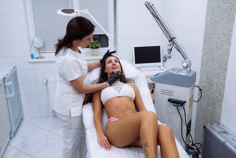 Kobiety fabrykują w klinice Piękne żeńskie twarzy i cosmetologist ` s ręki z strzykawką podczas twarzowych piękno zastrzyków zdjęcia royalty free