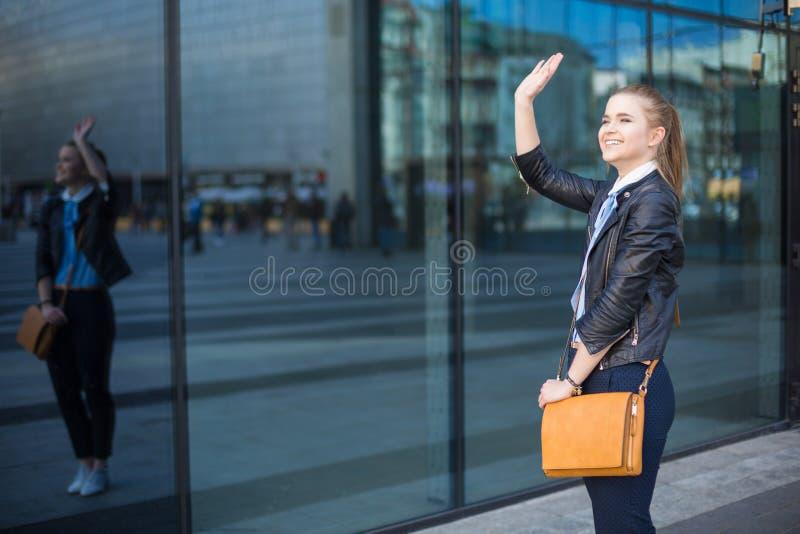 Kobiety falowania ręka w centrum miasta zdjęcia stock