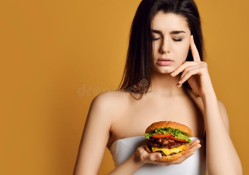 Kobiety główkowanie jeść dwoistą cheeseburger wołowiny kanapkę z głodnym usta Diety I fasta food poj?cie obrazy royalty free