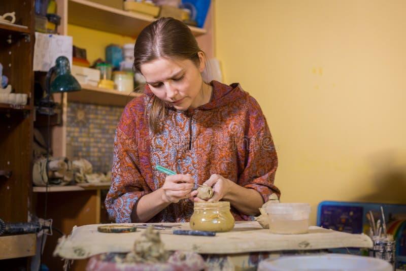 Kobiety garncarka robi ceramicznemu pamiątkarskiemu centowi gwizdać w ceramicznym warsztacie zdjęcie royalty free