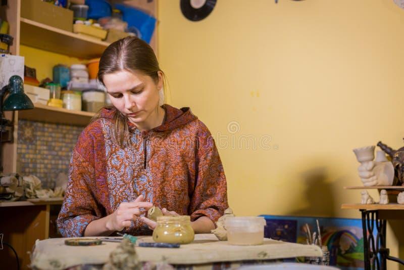 Kobiety garncarka robi ceramicznemu pami?tkarskiemu centowi gwizda? w ceramicznym warsztacie fotografia royalty free