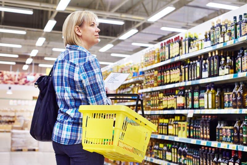 Kobiety gospodyni domowa z lista zakupy w wydziałowego sklepu rośliny oleju obraz stock