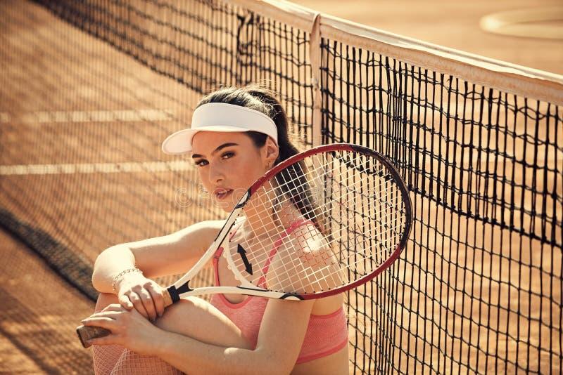 Kobiety gracz w tenisa jest ubranym nakrętkę ma odpoczynek zdjęcia royalty free