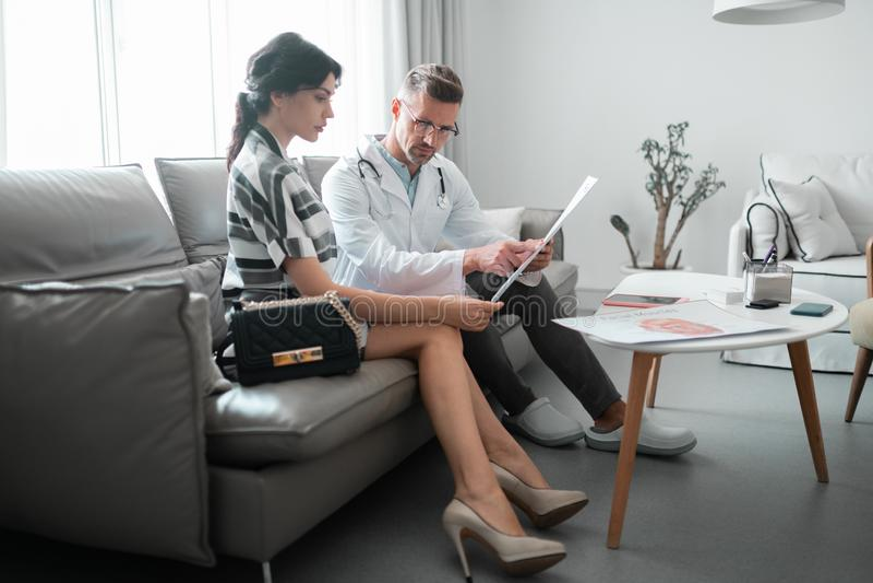 Kobiety i chirurga plastycznego obsiadanie na kanapy planowaniu stawia czoło korekcję zdjęcia stock