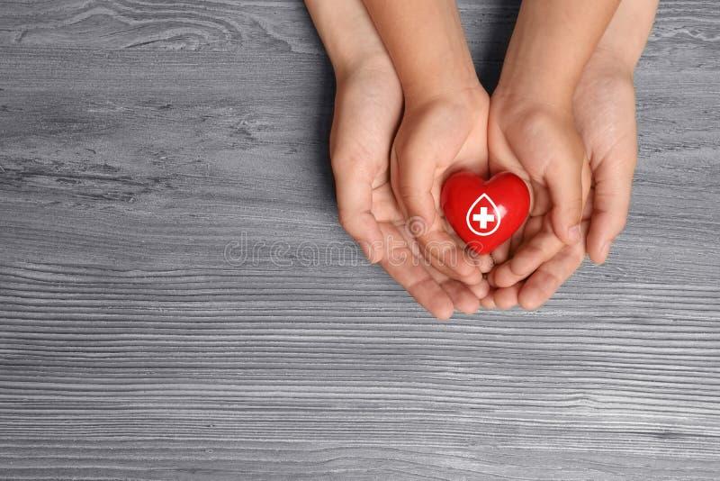 Kobiety i dziecka mienia serce na drewnianym tle, odgórny widok z przestrzenią dla teksta fotografia stock