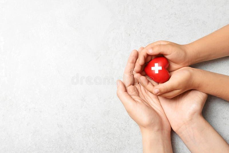 Kobiety i dziecka mienia serce na popielatym kamieniu, odgórny widok z przestrzenią dla teksta Darowizny poj?cie zdjęcia stock