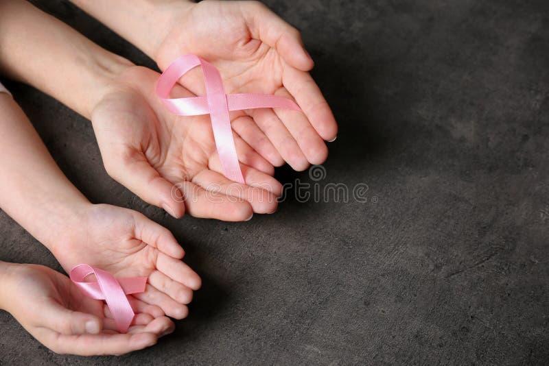 Kobiety i dziewczyny mienie różowi faborki na popielatym tle, odgórny widok z przestrzenią dla teksta nowotwór piersi lekarstwa w fotografia royalty free